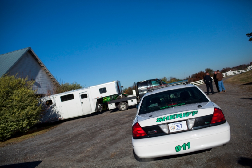 Two officers from the Blount County Sheriff's office stand with McNutt Farm owner, William McNutt, in front of the transport truck and trailer on November 8, 2013. Due to concerns over security, the transport vehicle removed its license plates and any identifying markings, and received a police escorted to McNutt Farm. (Photo: Adam McCauley)