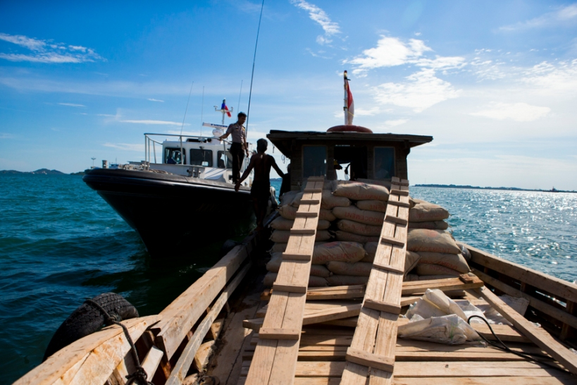 "Indonesia's marine police stop a vessel during their afternoon patrol off the coast of Batam Island. When asked why, officers noted the ship ""looked wrong"" and wanted to investigate. Beyond piracy, marine authorities contend with high rates of international smuggling in Southeast Asia. (Photo: Adam McCauley)"