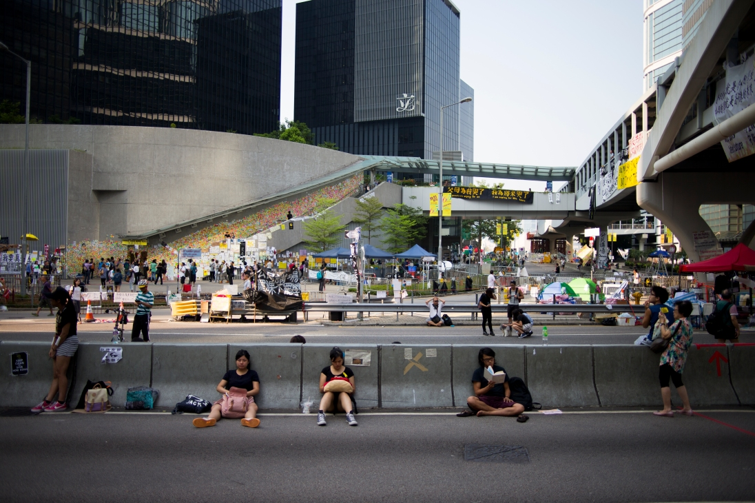 "Students read, do their homework, or rest, on Harcourt Road in Hong Kong on October 7, 2014. This usually busy four-lane highway has served as town square to thousands of Hong Kong residents during the #OccupyCentral protests. In the background, the every expanding ""Lennon Wall"" features messages of support written on bright post-it notes. (Photo: Adam McCauley)"
