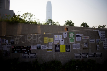 A man walks down the paved walkway that separates Tamar Park from Tim Mei Avenue, in central Hong Kong. The walkway is plastered with banners and signs in support of the #OccupyCentral protests. (Photo: Adam McCauley)