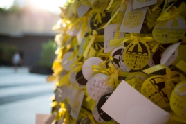 """Yellow ribbons and logos of reading """"Umbrella Revolution"""" ring a pillar outside the government offices adjacent Tamar Park. The OccupyCentral protests assumed the title, Umbrella Revolution, after protestors used the household tools to defend themselves against pepper spray deployed by Hong Kong Police. (Photo: Adam McCauley)"""