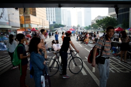 A biker rides down the pedestrian-filled Harcourt Road to survey the tenth day of #OccupyCentral protests in Hong Kong. (Photo: Adam McCauley)